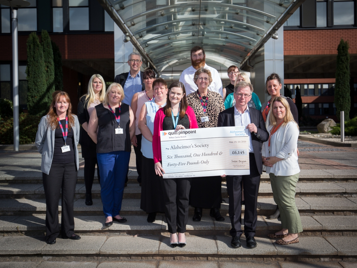 Quill Pinpoint team presenting check to the Alzheimer's Society